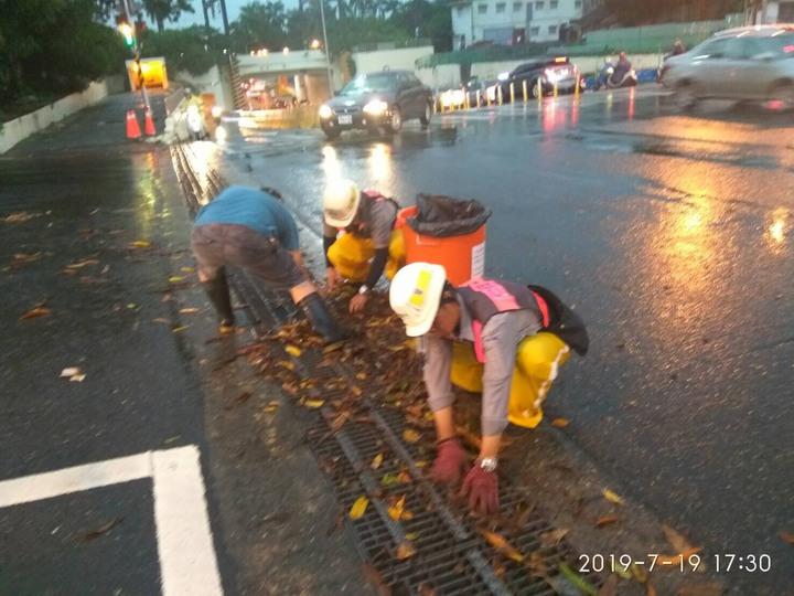 台南傍晚下起豪大雨,環保局人員在小東路清除樹葉與雜物阻塞,避免阻礙水流,水利局人員開啟水溝蓋加速排水。圖/水利局提供