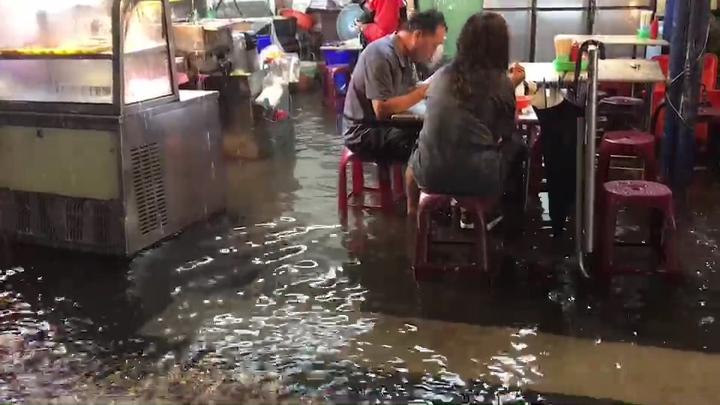 一場暴雨使原本不淹水的北港市區,有民眾腳泡著水還能一邊吃飯,成為有趣的雨中即景。記者蔡維斌/攝影