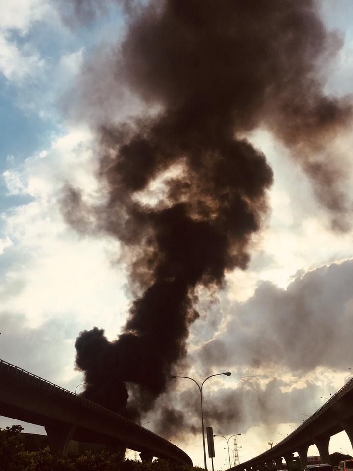 桃園市龜山區一處連棟式鐵皮倉儲今天下午3點多竄出大火,火場濃濃黑煙飄散直竄天際,由於緊鄰國道1號,不少用路人見狀放慢車速,也有乘客拍下濃煙景象,直呼是「黑煙蔽日」。記者陳俊智/攝影
