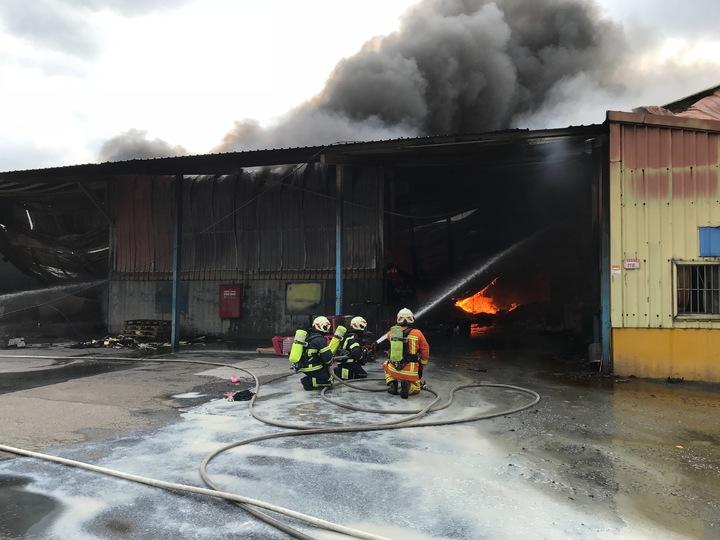 桃園市龜山區一處連棟式鐵皮倉儲今天下午3點多竄出大火,消防員獲報灌救。圖/桃園市消防局提供