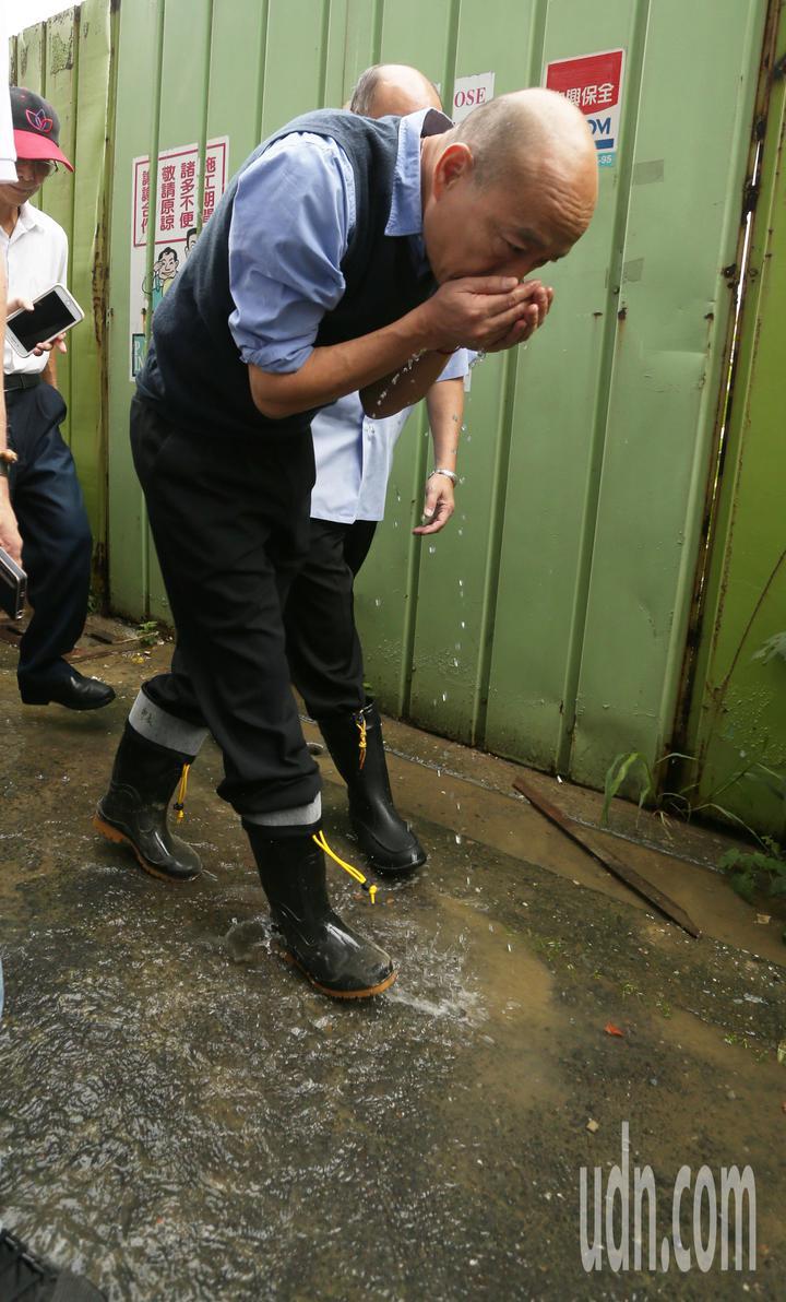 高雄市長韓國瑜今天下午臨時安排行程,到苓雅區一棟大樓視察地下室淹水情況,他還親自撈起積水聞是否有汽油味。記者劉學聖/攝影