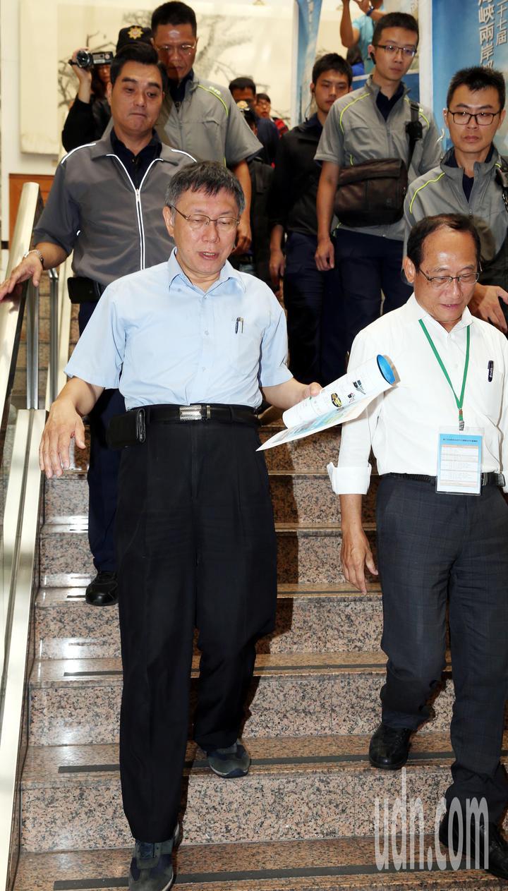 台北市長柯文哲(前左)在大批維安人員陪同下離開「海峽兩岸都市交通學術研討會」會場。記者侯永全/攝影