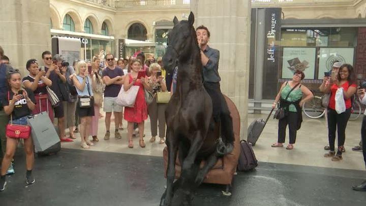 法國巴黎某個火車站,21日出現「馬上」藝術快閃演出,兩名演出者坐在馬背上,在車站與站內餐廳走動,表演特技,給乘客意外驚喜。路透社