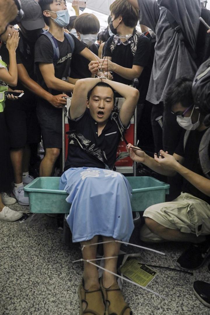 香港國際機場13日下午再度被「反送中」群眾癱瘓,《環球網》香港特派記者付國豪(中)遭抗議者指控是臥底,一度遭到拳打腳踢、辱罵與淋水,但因反嗆「我支持香港警察,你可以打我了」獲中國網民力挺。美聯