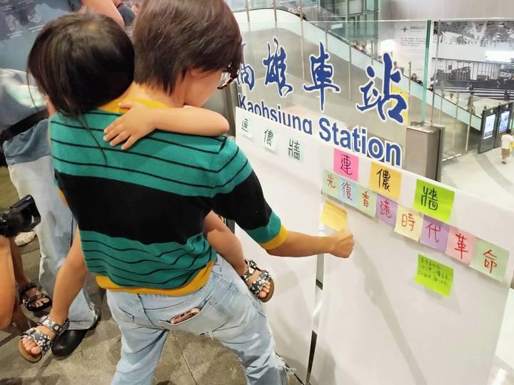 林姓女子抱著女兒在珍珠板「連儂牆」,貼上聲援香港的字句。記者林保光/攝影