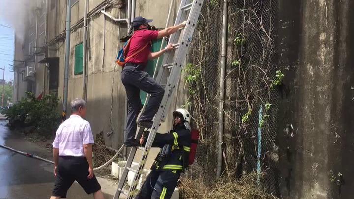 苗栗縣頭份市中華路一間自助餐店2樓今天下午1點多發生火災,救災人員攀梯救出屋內2人。圖/溫文銍提供