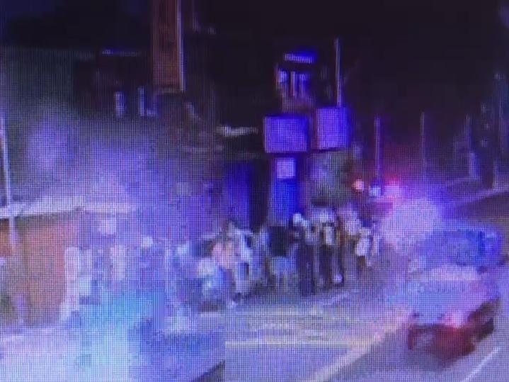 事發後店外聚集逃出的顧客,警方也到場處理情況。記者巫鴻瑋/翻攝