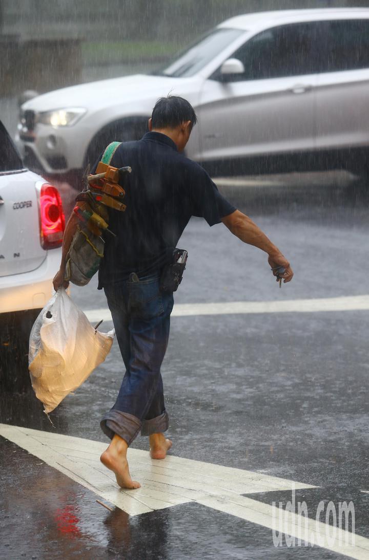 午後,台北市下起傾盆大雨,雨勢來得又快又急,持續超過一個小時,一位工人等不及大雨停,乾脆打赤腳直接在大雨中行走。記者杜建重/攝影