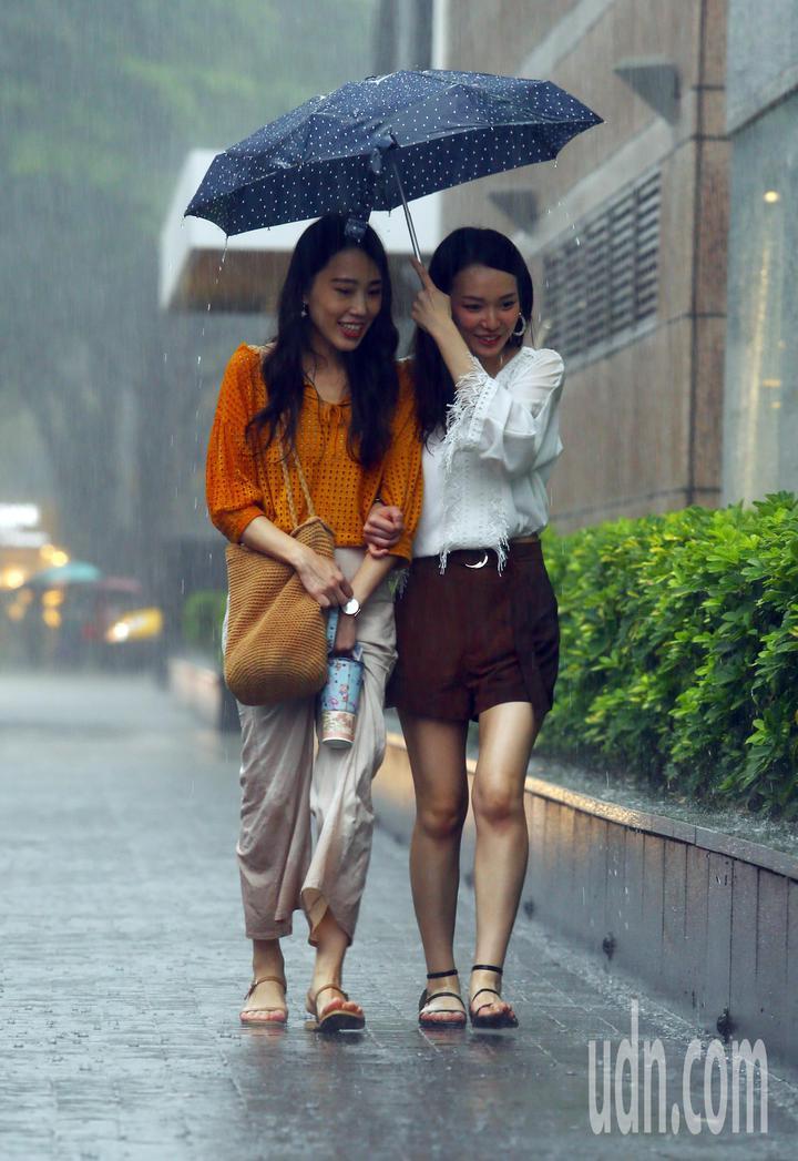 北部地區下午下起大雷雨,行人撐傘走在路上,雖然拉起褲腳避免被雨淋溼,但雨勢太大,似乎起不了什麼作用。記者杜建重/攝影