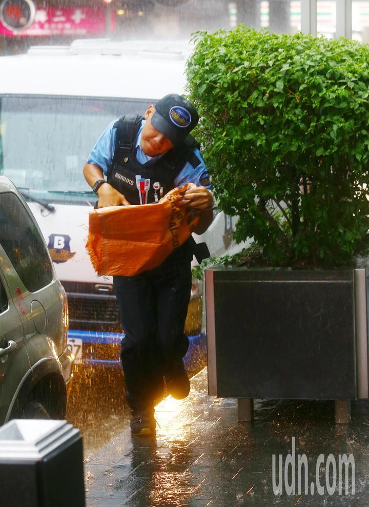 台北市下午下起大雷雨,一位保全工作人員從車上跑下來,為了躲雨,連頭都歪了。記者杜建重/攝影