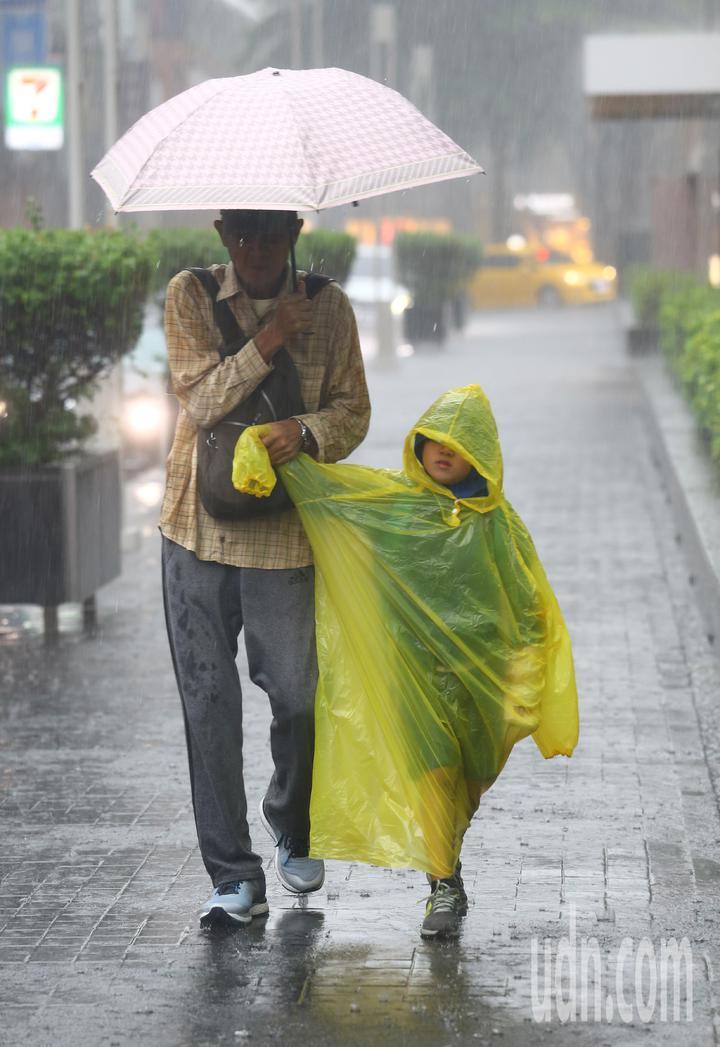 台北市下午兩點忽然下起傾盆大雨,雨勢過大,大人撐傘不夠,小朋友還得穿上雨衣才能遮雨。記者杜建重/攝影