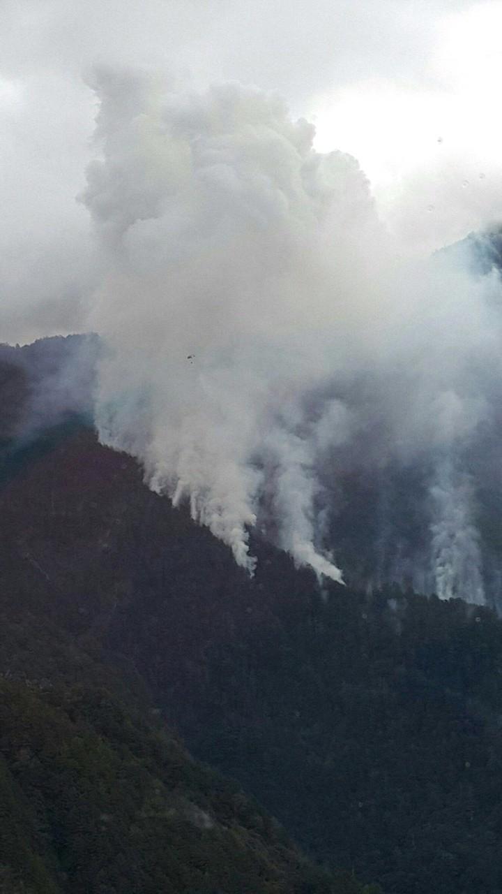 空勤總隊直升機到高山協助滅火,在大火濃煙中,可看到直升機只剩一個黑點,任務危險。圖/空勤總隊提供